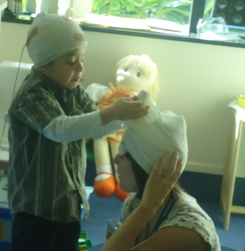 A boy applies a bandage to an adult's head as part of therapeutic play.