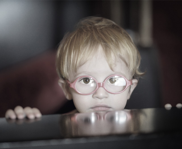 A child in upside down glasses looking up over a table
